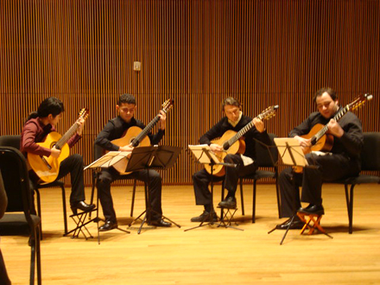 4 guitarists playing on stage